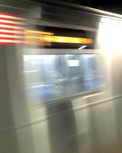 The New F Train Glides Into the Station - my camera phone tries to keep up.